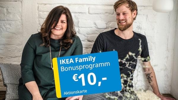 Eine Frau und ein Mann sitzen neben einander auf einer Bank von IKEA