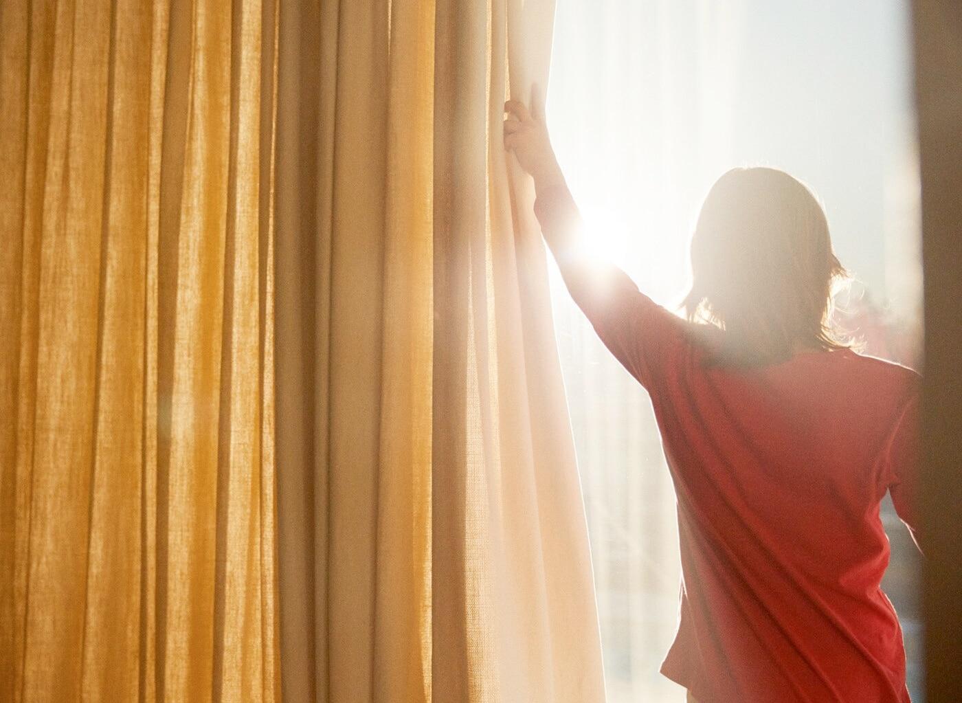 Eine Frau zieht die Gardine am Fenster zur Seite, um die Sonne zu begrüssen.