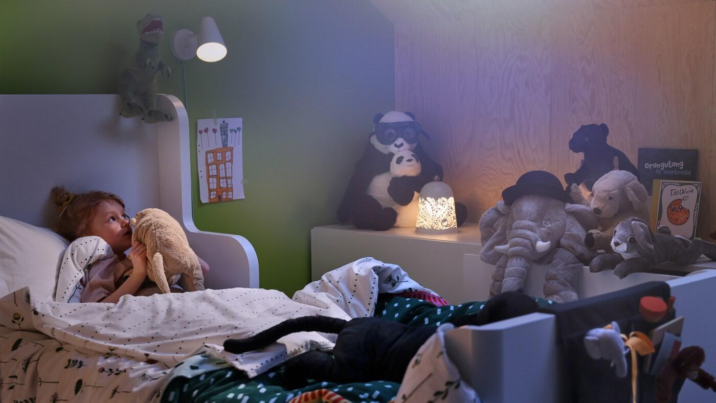 Eine FUBBLA Wandleuchte und eine SOLSKUR LED-Tischleuchte erhellen ein kuscheliges Kinderzimmer. Ein Kind liegt im Bett und flüstert seinem Lieblingsstofftier etwas ins Ohr.