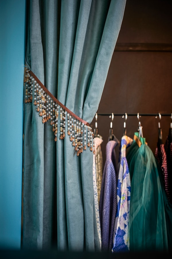 Eine Gardine vor einem Kleiderschrank, in dem Kleidung zu sehen ist.