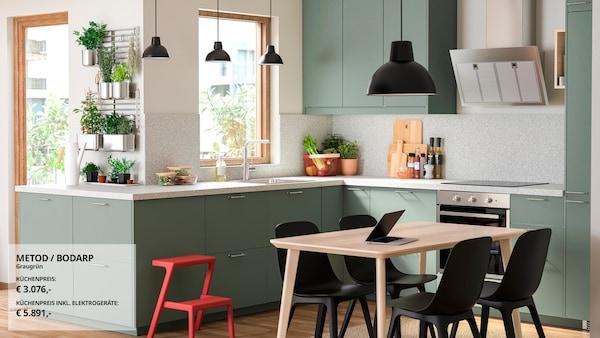Eine grau-grüne Küche mit Wandschränken, Edelstahlspüle, Arbeitsplatte, Dunstabzugshaube, Heißluftofen, Regal und Hängeleuchte.