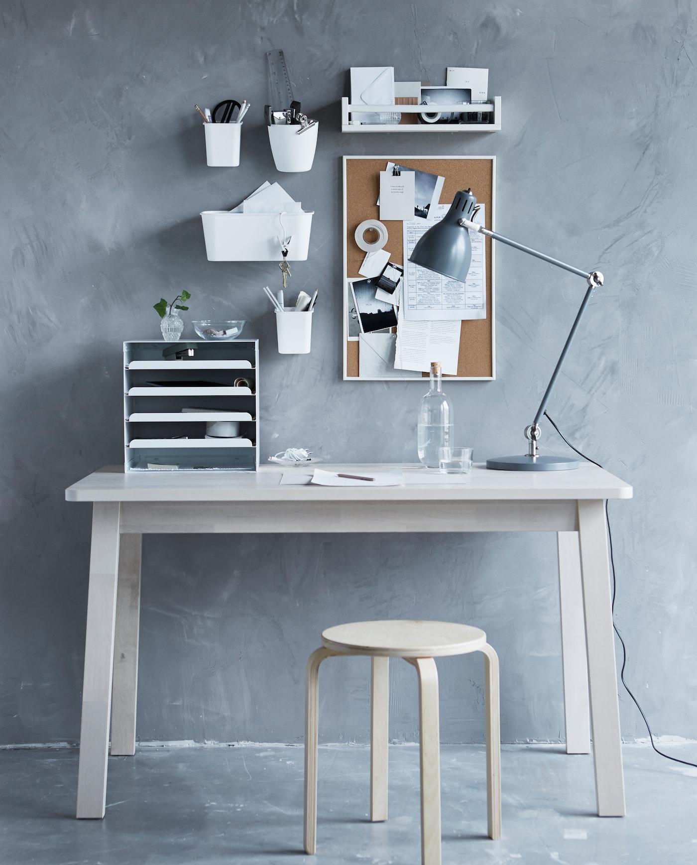 Eine graue Wand mit einer Pinnwand, einem Regal & Blumentöpfen, davor ein weißer Schreibtisch mit Hocker.