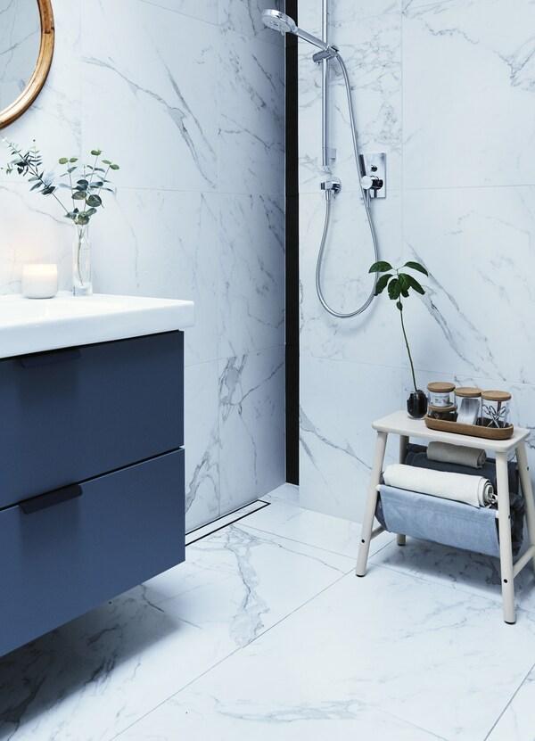 Eine graue Waschkommode in einem weiß gehaltenen Bad, u. a. mit VILTO Hocker mit Aufbewahrung Birke.