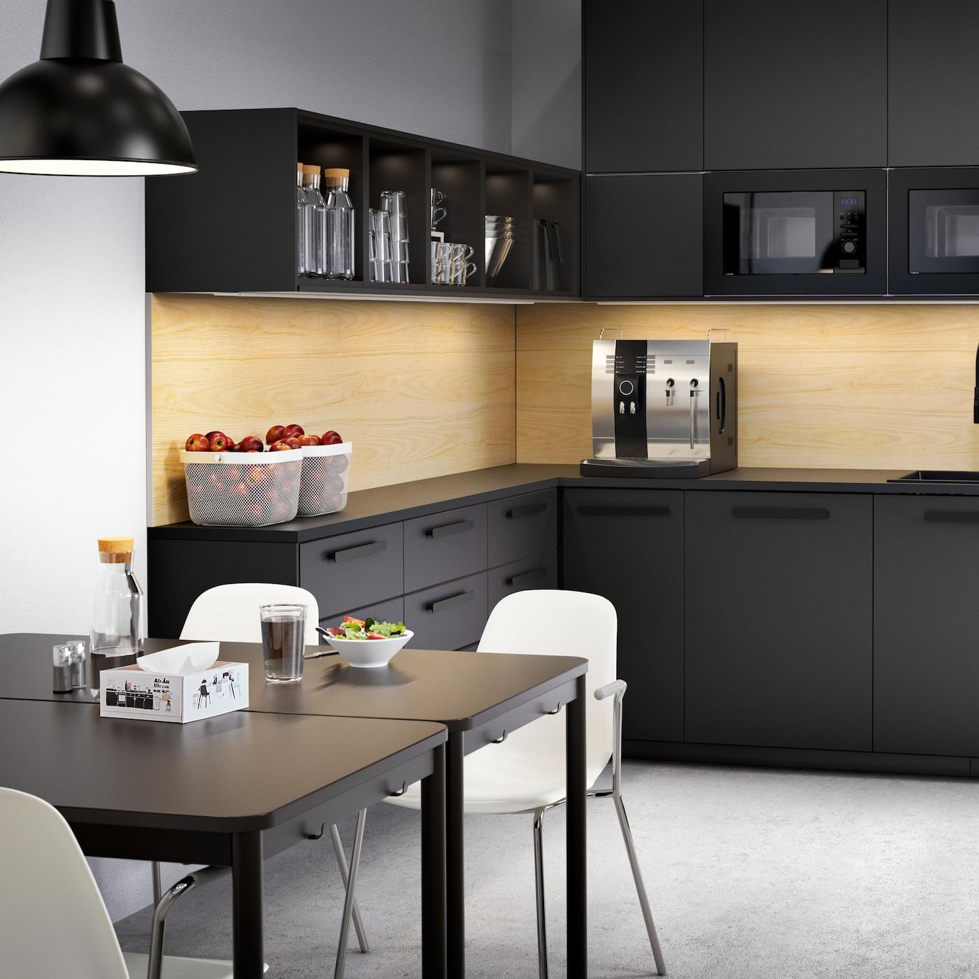 Eine große anthrazitfarbene Küche mit Schubladen und Schränken, Kaffeemaschine, Obstschalen und zwei Tischen mit weißen Stühlen.