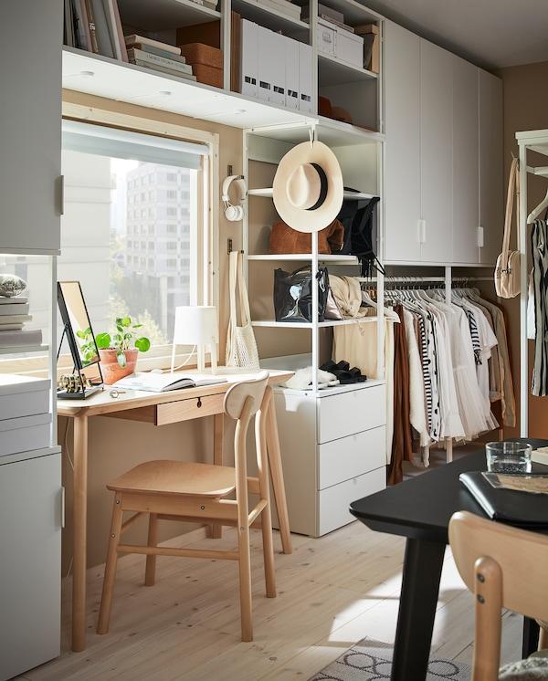 Eine große PLATSA Aufbewkomb.+6 Türen/3 Schubladen ist rund um ein Fenster angeordnet, vor das perfekt ein Schreibtisch passt.