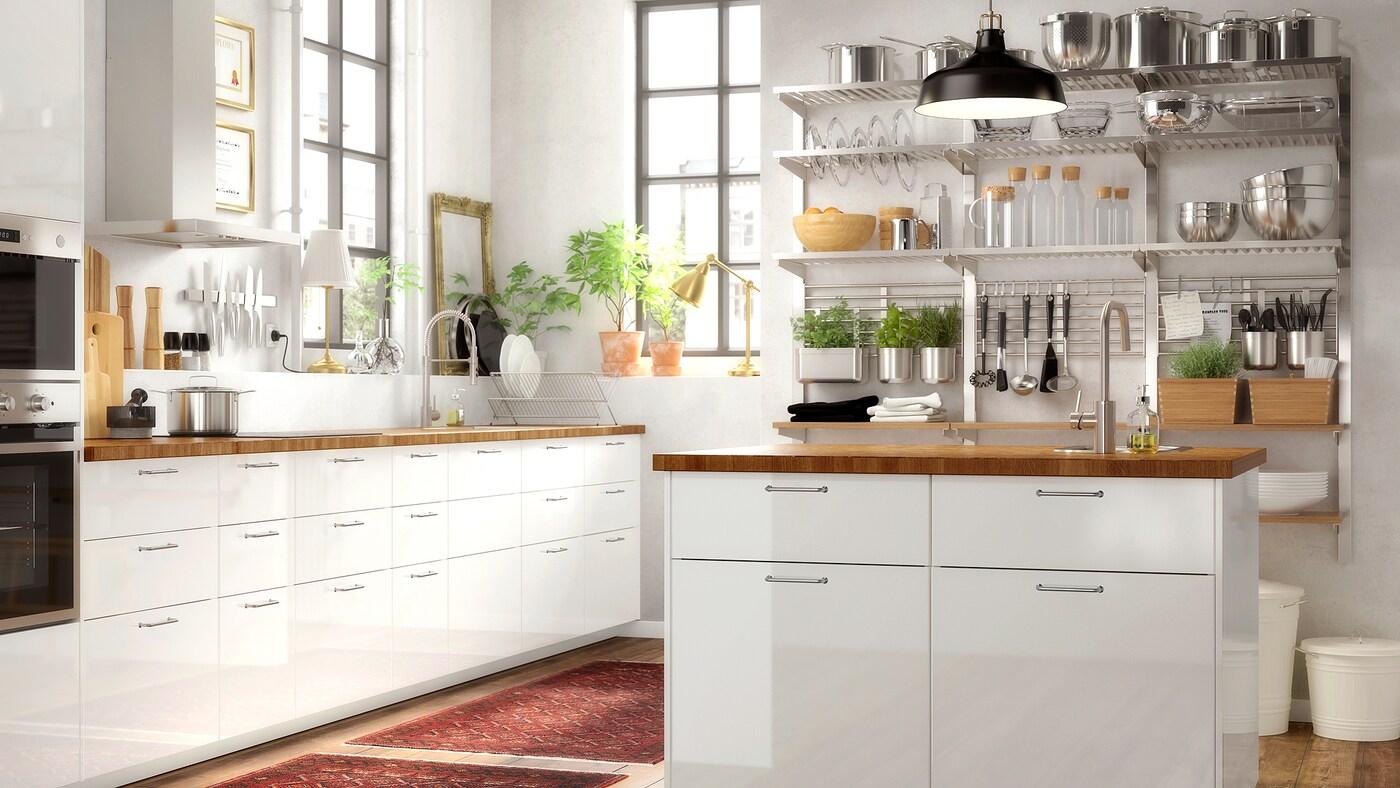 Eine große weiße Küche mit einer Kücheninsel und hochglänzenden weißen Fronten, Arbeitsplatten aus Eiche und offenen Regalelementen an der Wand