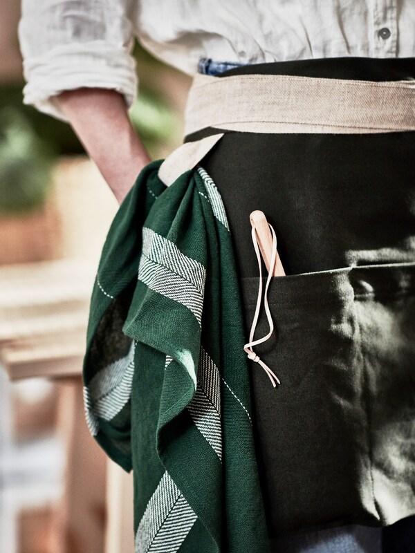 Eine Großstadtheimgärtnerin in einer handgefertigten grünen Schürze aus Jute und Baumwolle