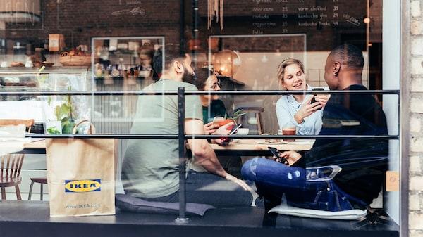 Eine Gruppe junger Menschen sitzt gemeinsam in einem Café, neben ihnen steht eine IKEA Papiertüte.