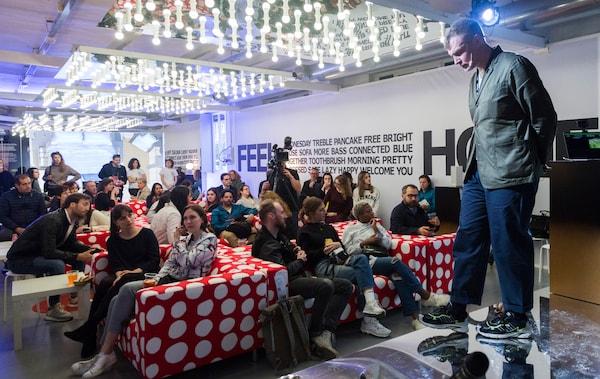 Eine Gruppe Leute sitzt in einem großen Raum auf rotweißen Sofas und hört einer Person zu, die auf einer Bühne steht und etwas erzählt.