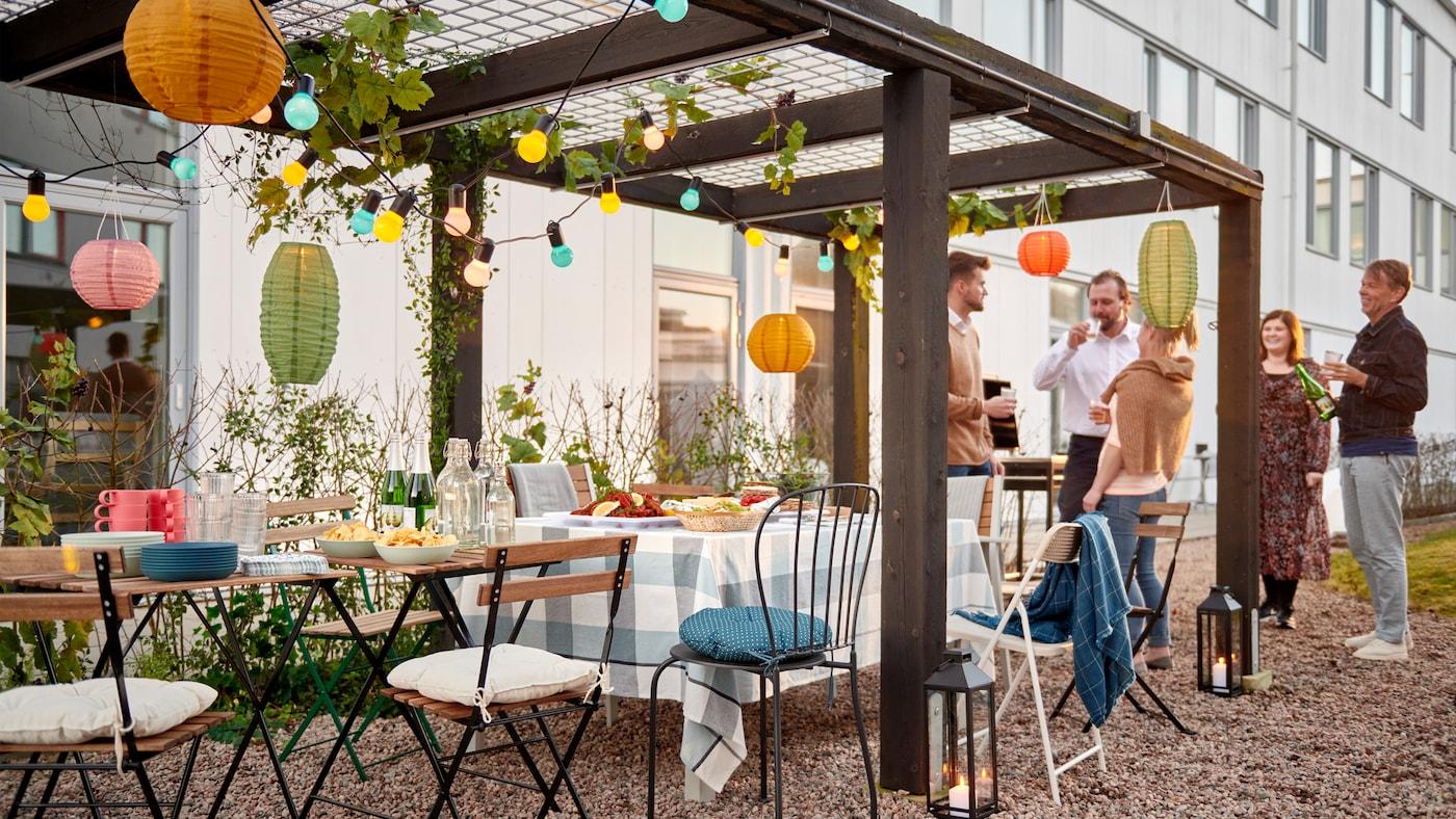 Eine Gruppe von Menschen, die neben einer Reihe von Stühlen und kleinen Tischen stehen, die für eine Party unter einer dekorierten Pergola in einem Innenhof gedeckt sind.
