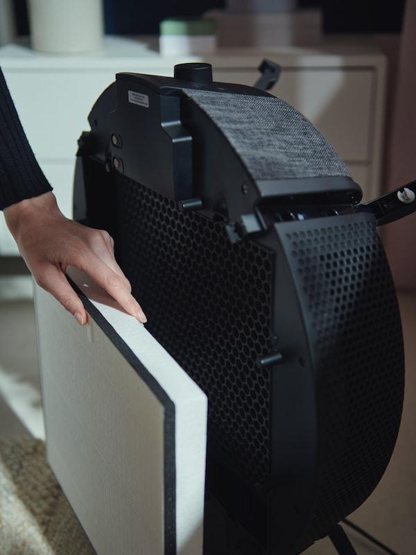 Eine Hand entnimmt den Partikelfilter hinter der Front eines schwarzen Luftreinigers aus der STARKVIND Serie.