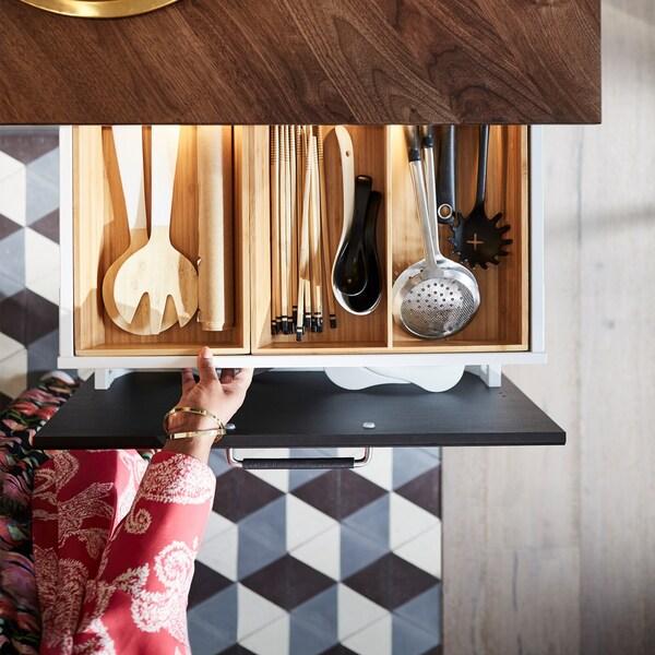 Eine Hand öffnet eine Schublade unter einer dunklen Holzarbeitsplatte. Darin ist ein Holzeinsatz mit Küchenutensilien zu sehen.