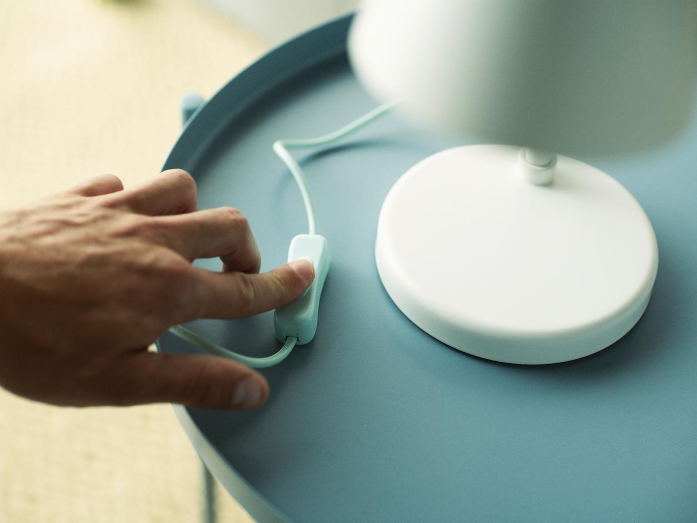 Eine Hand schaltet das Licht einer weißen Tischleuchte auf einem hellblauen Tisch aus.