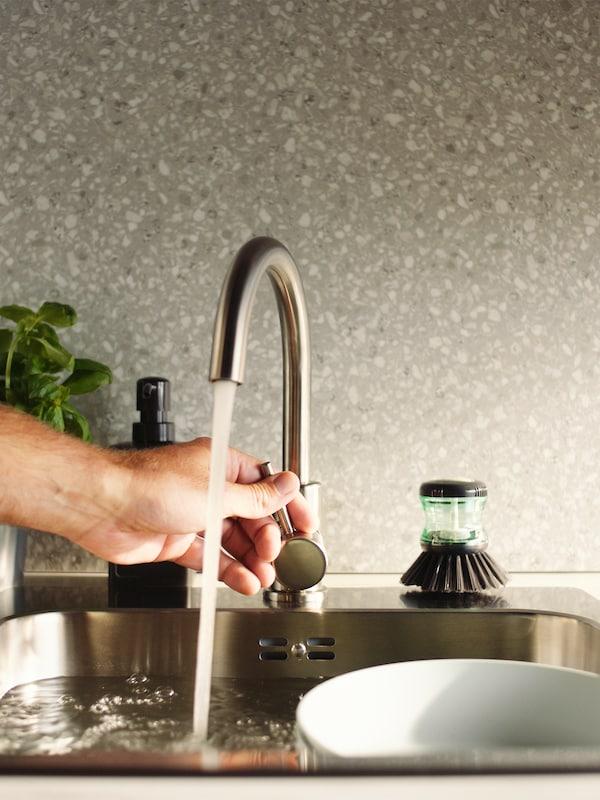 Eine Hand stellt den Wasserstrahl einer GLYPEN Mischbatterie ein, daneben liegt eine TÅRTSMET Spülbürste.