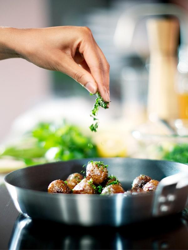 Eine Hand streut Kräuter über die HUVUDROLL Proteinbällchen in einer IKEA 365+ Bratpfanne.