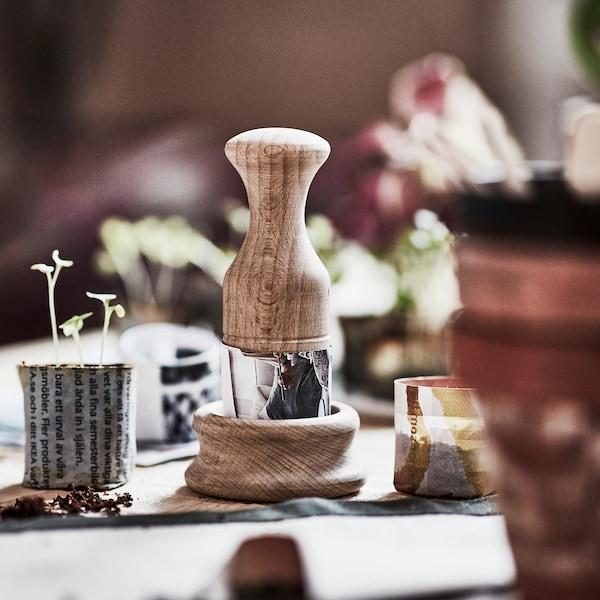 Eine handgearbeitete Form für Papierblumentöpfe aus Buche steht auf einem Tisch mit kleinen Papiertöpfen mit Setzlingen.