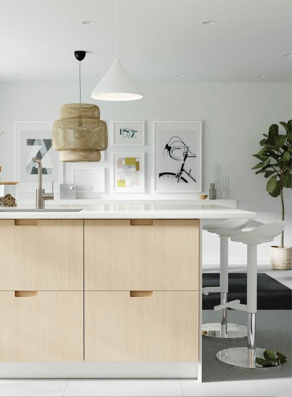 Eine helle Küche mit Bambusfronten und weißen Barhockern vor einer stilvollen Galeriewand.