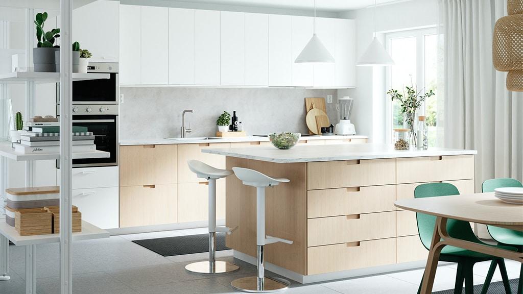 eine helle küche mit einer kücheninsel, 2 Barhockern und einem Esstisch davor