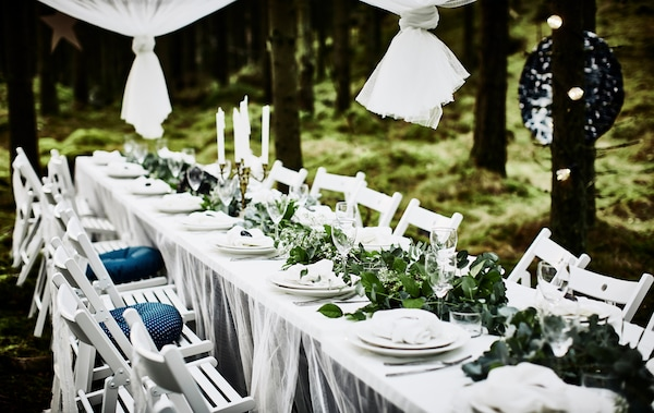 Eine Hochzeitstafel im Wald mit weißer Tischplatte, Spitzengardinen als Tischdecken, weißen Klappstühlen, weißem Geschirr und einem Tischläufer aus Grünzeug
