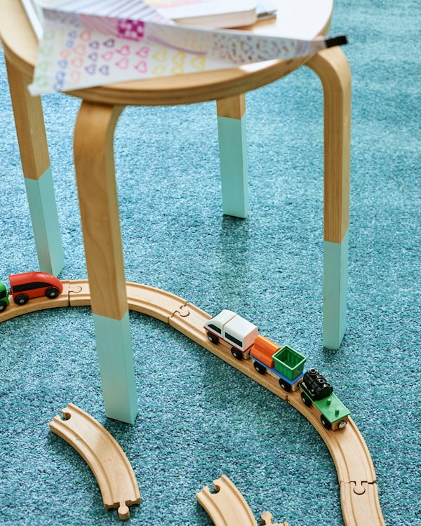 Eine Holzeisenbahn fährt zwischen den Beinen eines Hockers über einen LANGSTED Teppich.