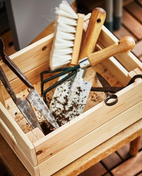 Eine Holzkiste gefüllt mit Gartenutensilien