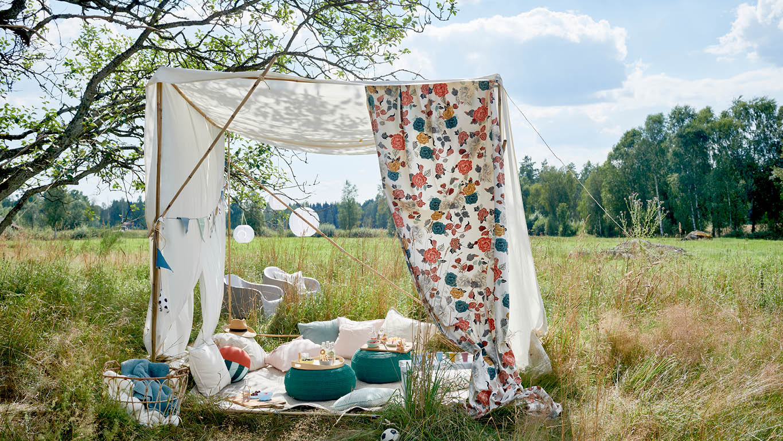 Eine Holzkonstruktion und Seile auf denen lange Stücke Meterware in Bunt befestigt sind, ergeben ein kuscheliges Sommerzelt für Picknicks.