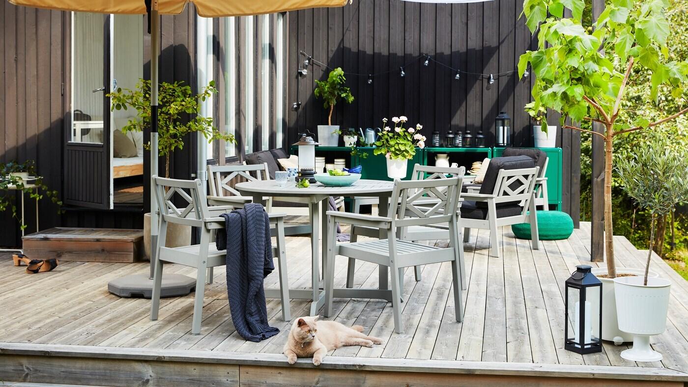 Eine Holzterasse mit einem beige farbenen Sonnenschirm und grauen Outdoor Möbeln, grünen Pflanzen und einer Katze.