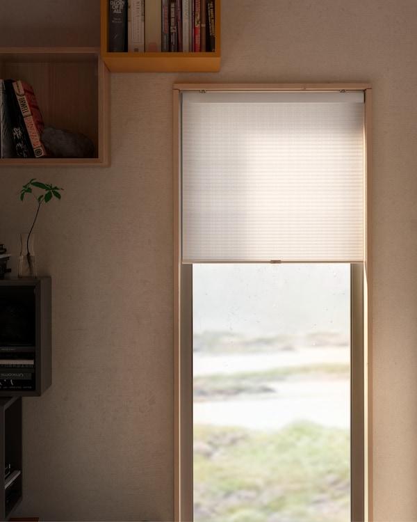 Eine HOPPVALS Wabenjalousie in Weiß vor einem Fenster