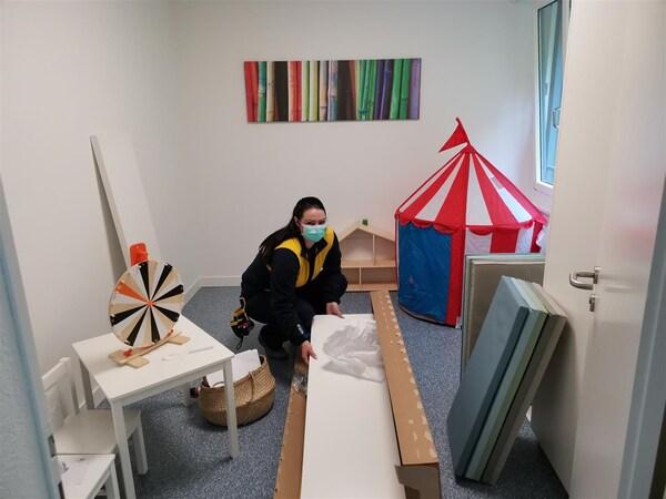 Eine IKEA Mitarbeiterin packt ein Möbelstück in der Herberge für Frauen in Zug aus, um es zu montieren