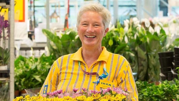 Eine IKEA Verkaufsmitarbeiterin steht in der Pflanzenabteilung und lächelt