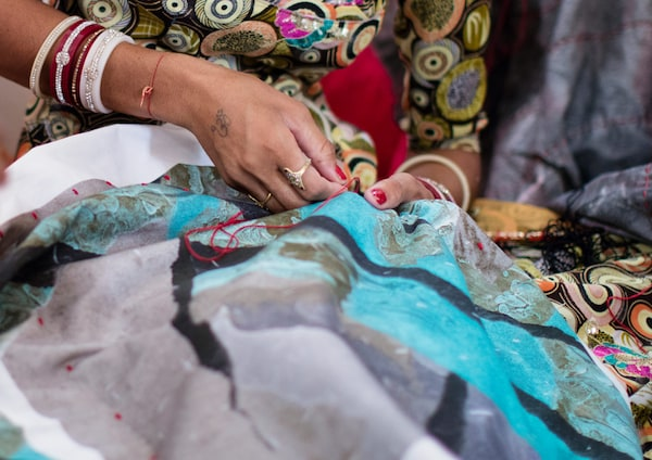 Eine indische Kunsthandwerkerin bestickt einen Kissenbezug mit einem modernen, unregelmässigen Druck in Türkis, Grau und Schwarz.