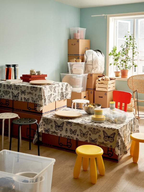 Eine Innenansicht eines Raums während eines Umzugs. JÄTTENE Umzugskartons sind aufeinandergestapelt und bilden einen Tisch in zwei Höhen für eine einfache Mahlzeit. Darum stehen Sitzgelegenheiten.
