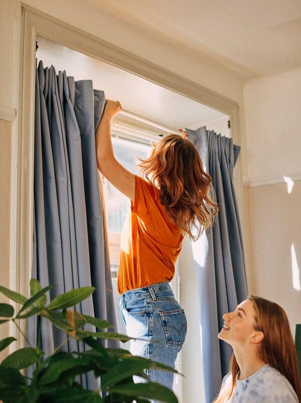 Eine junge Frau nutzt eine BOTAREN Duschvorhangstange, um eine Gardine ohne Bohren vor dem Fenster zu befestigen.