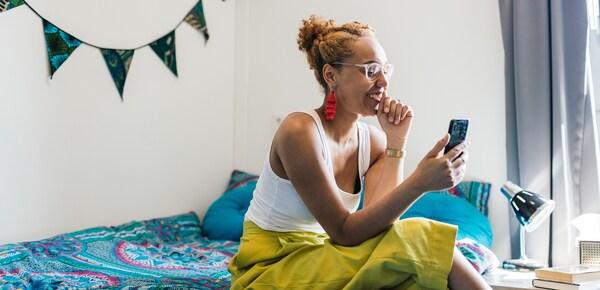 Eine junge Frau trägt knallgelbe Hosen, ein weißes Top und eine Brille und sitzt auf ihrem Bett. Sie schaut auf ihr Handy und lächelt.