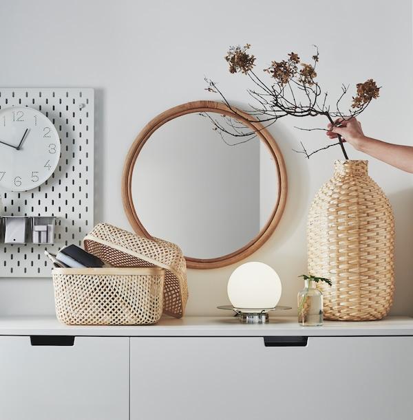 Eine KAFFEBÖNA Dekovase und eine SMARRA Box mit Deckel aus Bambus unter einem HINDÅS Spiegel.