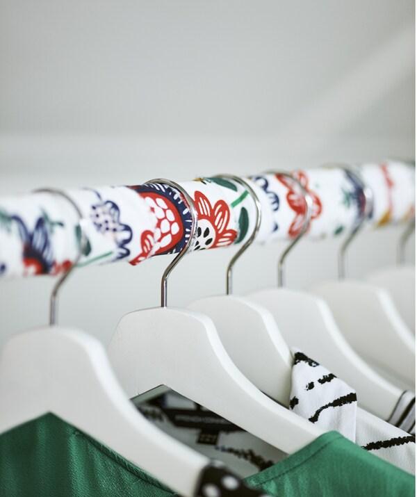 Eine Kleiderstange mit Stoffüberzug und BUMERANG Kleiderbügeln in Weiss