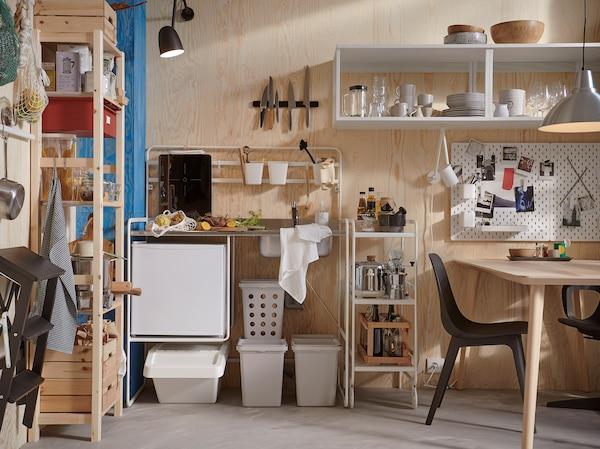 Eine kleine, helle Küche mit einer SUNNERSTA Miniküche, grauen Recyclingbehältern, einem Aufbewahrungssystem aus Kiefernholz und schwarzen Stühlen.