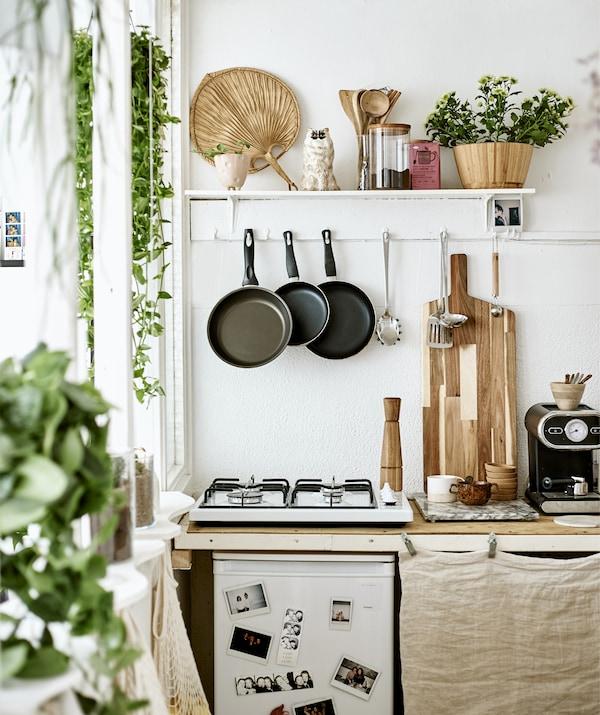 Eine kleine Küche mit Kochfeld, hängenden Utensilien und einem Regal zur Präsentation, u. a. mit AINA Meterware naturfarben.