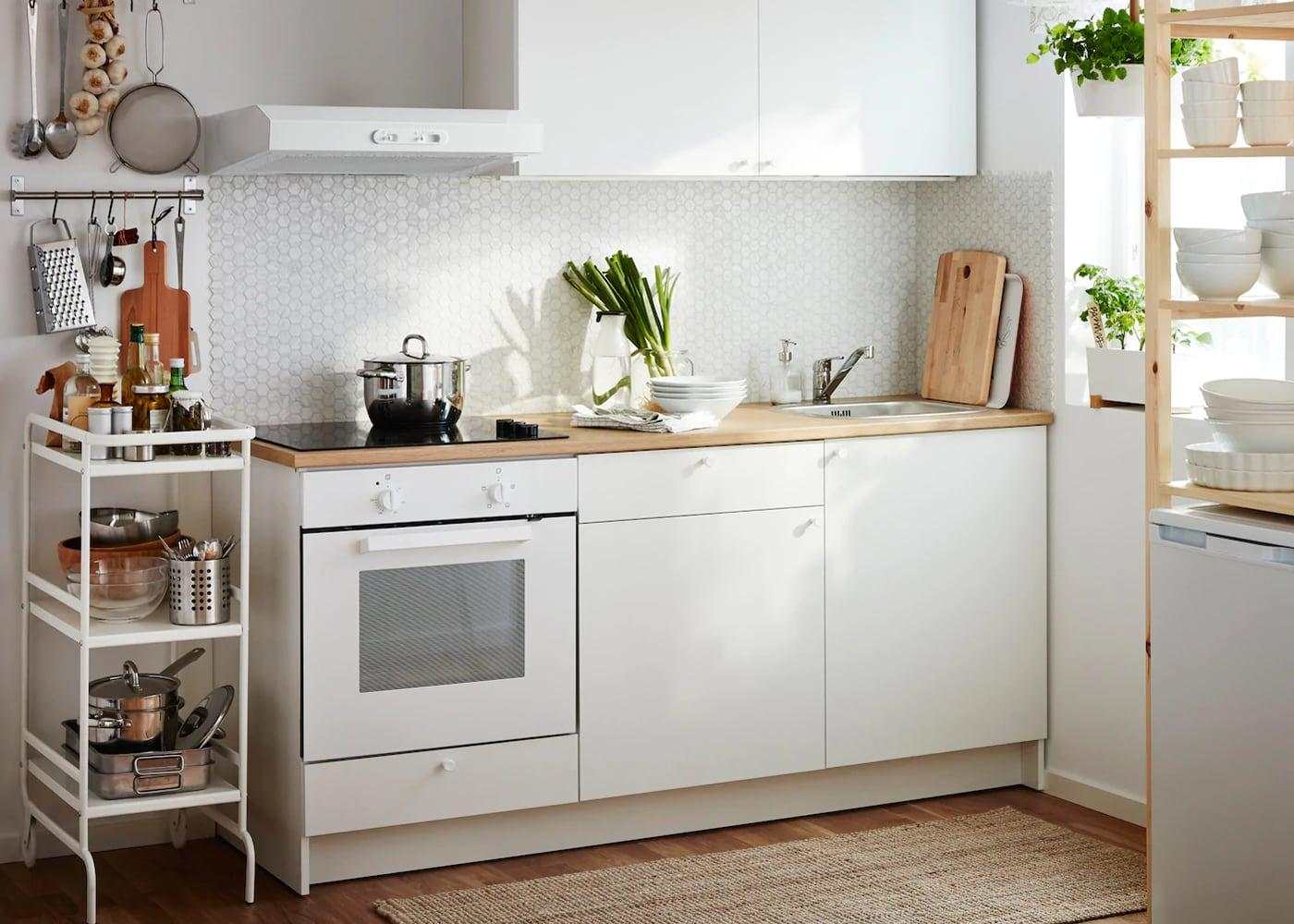 Eine kleine weiße Küche, bestehend aus einer Komplettlösung Unterschränke mit Türen, Schubladen, Arbeitsplatte und einem Wandschrank mit Türen. Kombiniert mit einer weißen wandmontierten Dunstabzugshaube, einem Ofen und einem schwarzen Glaskeramikkochfeld.