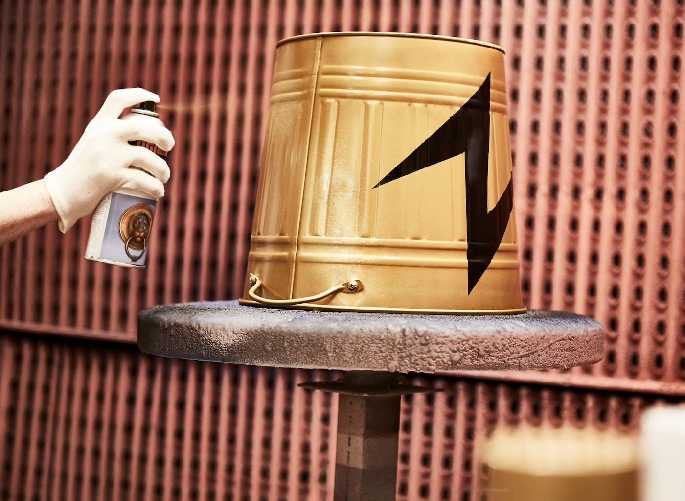 Eine KNODD Tonne wird mit einem Blitz-Motiv Gold angesprüht