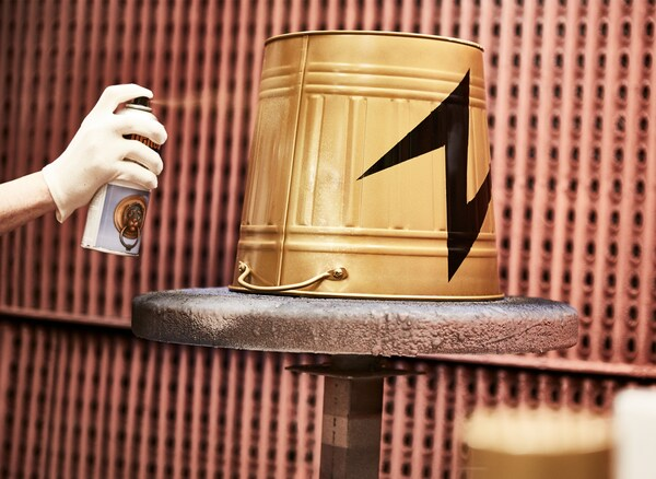 Eine KNODD Tonne wird mit goldener Farbe besprüht