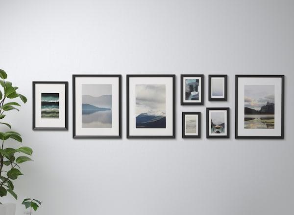 Eine Kollektion verschiedener Werke in schwarzen KNOPPÄNG Rahmen mit Bildern an einer weißen Wand
