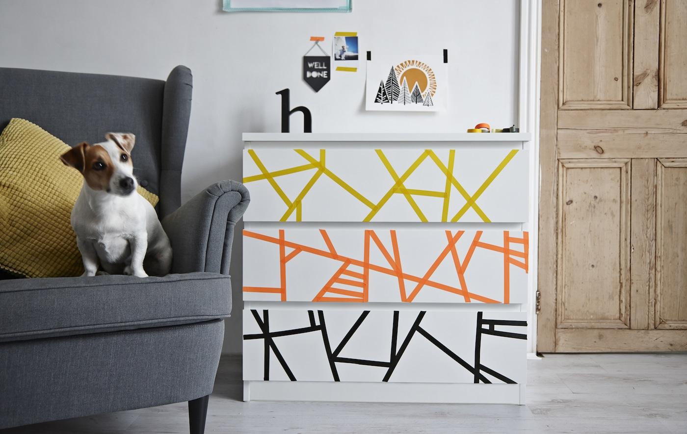 Eine Kommode, mit gelben, orangen & schwarzen Klebeband dekoriert, steht neben einem grauen Sessel mit einem Hund.