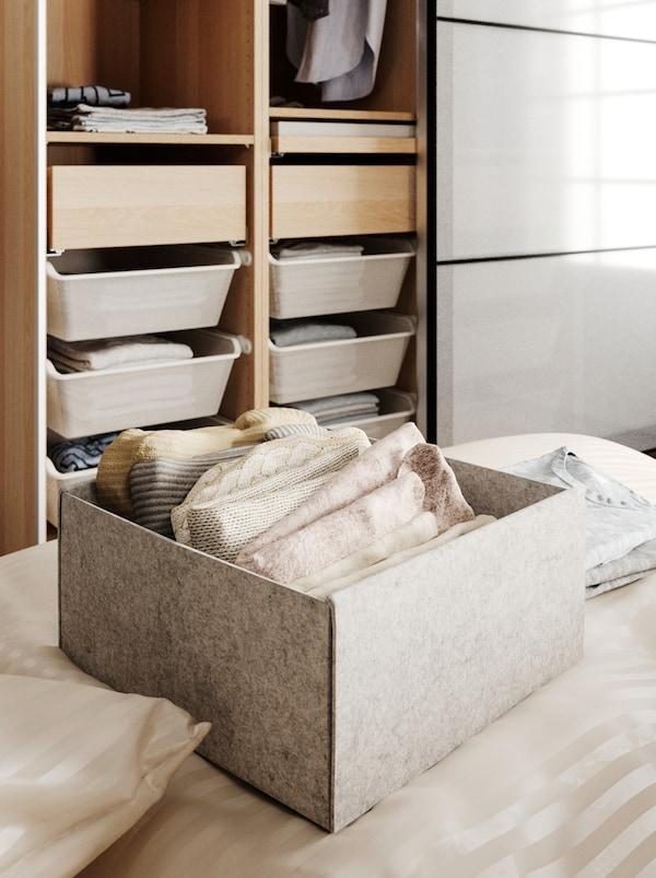 Eine KOMPLEMENT Box auf einem Bett. In der Box sind gefaltete Kleidungsstücke zu sehen. Dahinter steht an der Wand ein geöffneter Kleiderschrank mit verschiedenen Fächern.