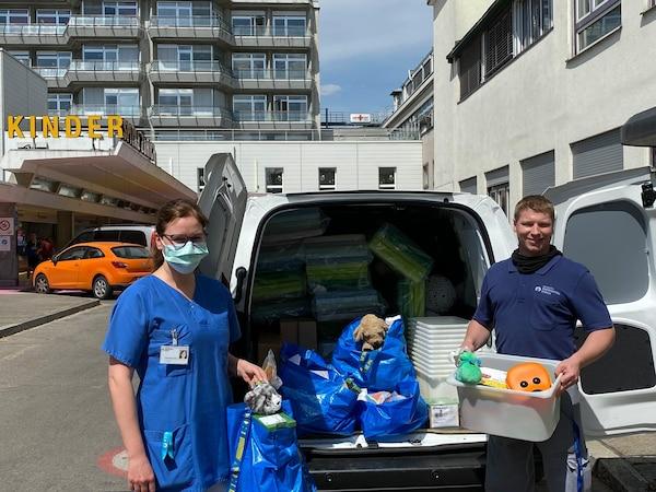 Eine Krankenschwester und ein IKEA MItarbeiter stehen vor einem Lieferwagen mit Spenden für das Kinderspital