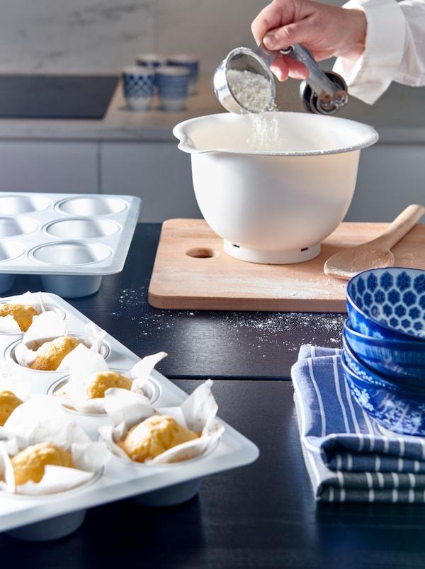 Eine Küche, in der gebacken wird. Eine Person schüttet Mehl in eine ENTUSIASM Schüssel, die neben einer Backform mit frisch gebackenen Muffins steht.