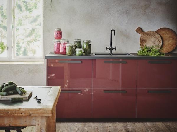 Eine Küche mit rotbraunen Fronten, einer schwarzen Arbeitsplatte, Griffen und Spüle im Kontrast zu einem ansonsten rustikal gehaltenen Raum mit einer grau verputzten Wand