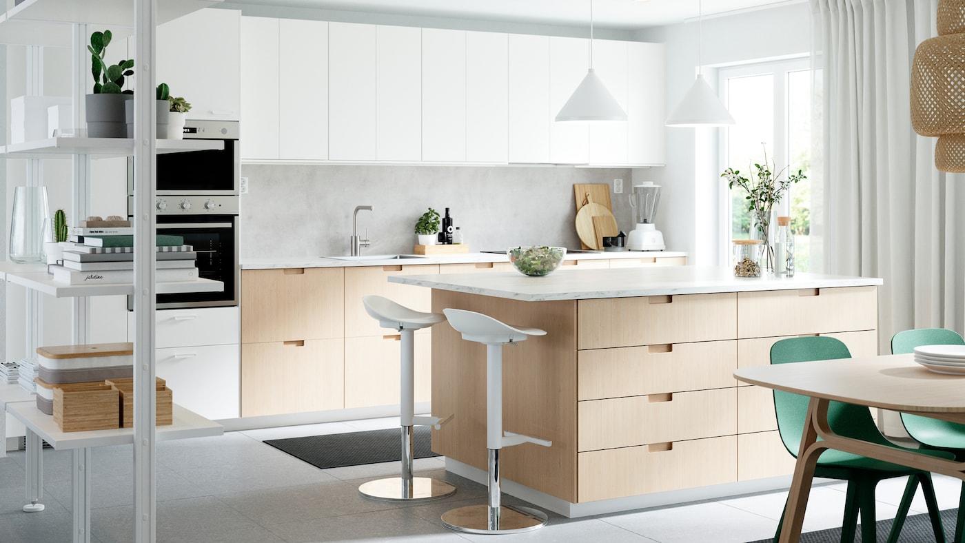 Eine Küche mit Schubladenfronten und Türen in Weiß/Bambus, einer Kücheninsel, zwei Barhockern, zwei Hängeleuchten und grünen Stühlen.