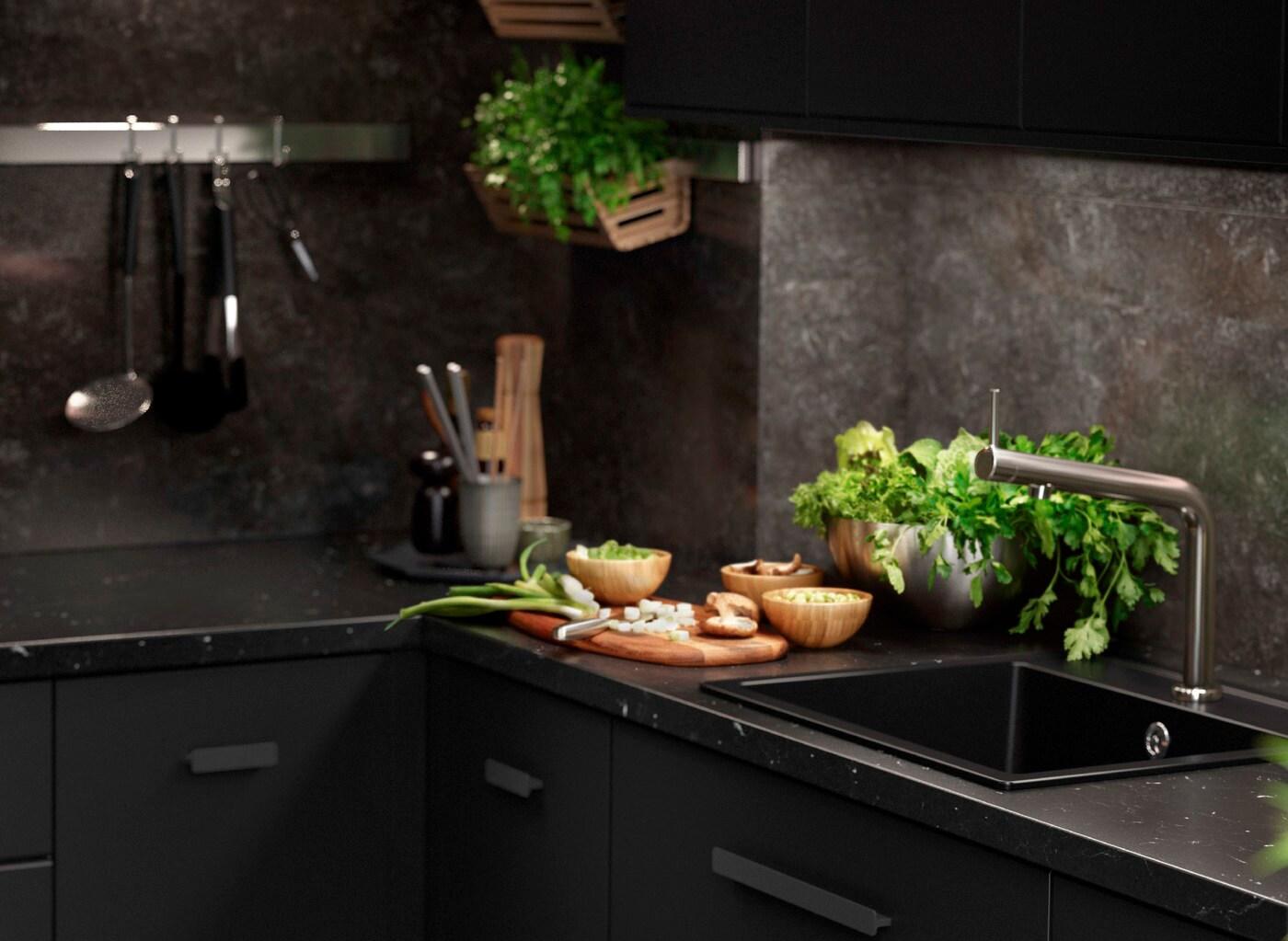 Eine Küche mit schwarzen KUNGSBACKA Fronten und Marmorflächen, dazu Küchenutensilien und frische Kräuter