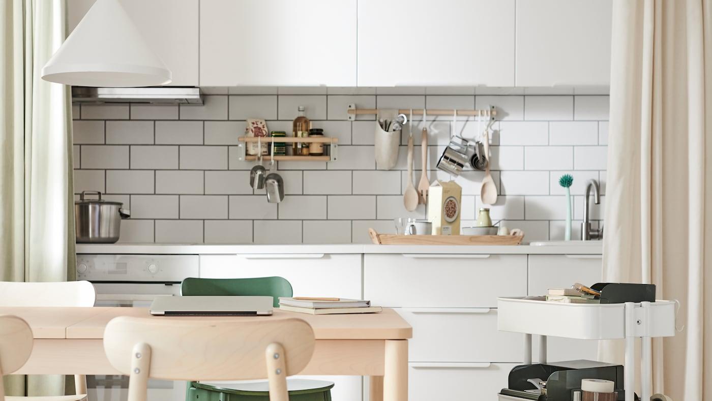 Eine Küche mit weissen Fliesen und weissen VEDDINGE Küchenfronten, u. a. mit Küchenutensilien, die an Haken von Stangen hängen.